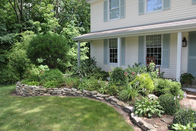 Painesville house with new stonework, flowerbeds, front flower beds, and japanese maple